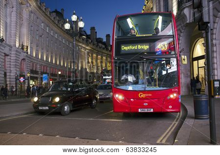 LONDON, UK - APRIL 16, 2014: London transport, Black taxi cab and red double-decker bus at Piccadilly Circus.