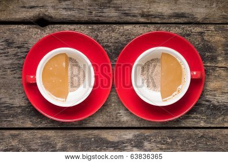 Half-full And Half Empty Cups Of Coffee On Wood Background