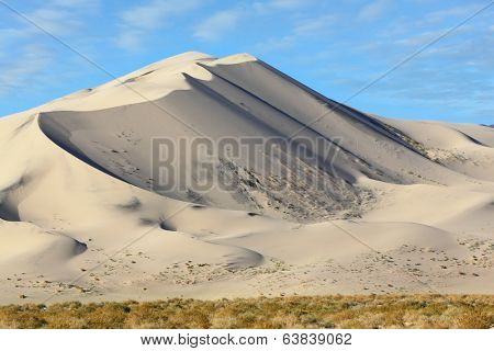 Eureka - a huge sand dune at sunrise. A thin ridge of dunes pale yellow. California, USA