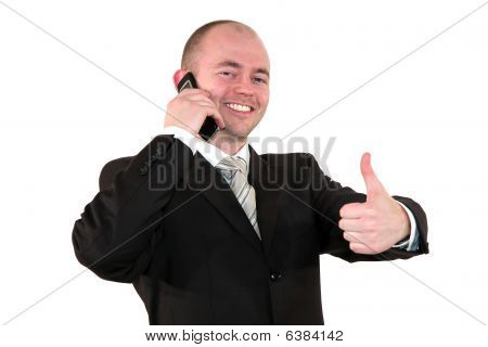 smiling young business man with cell phone posing with thumbs up sign