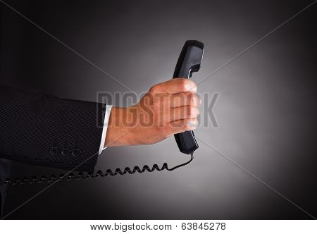 Hand Holding Telephone Receiver Over Black Background