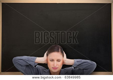 Close up of annoyed tradeswoman covering her ears against chalkboard with wooden frame