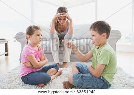 Fed up mother listening to her young children argue at home in the living room
