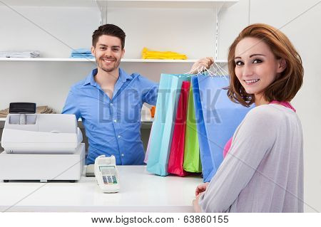 Cashier Handing Over Shopping Bag To Customer