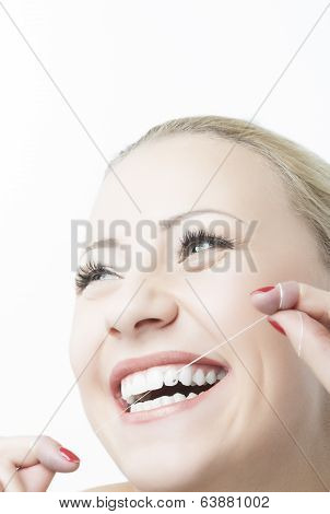 Caucasian Woman Flossing Teeth And Smiling. Dental Care And Oral Hygiene Concept