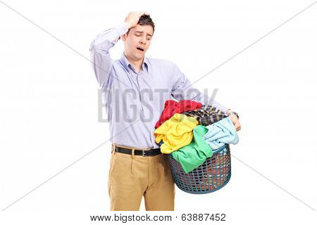 Unhappy man looking at a basket full of laundry isolated on white background