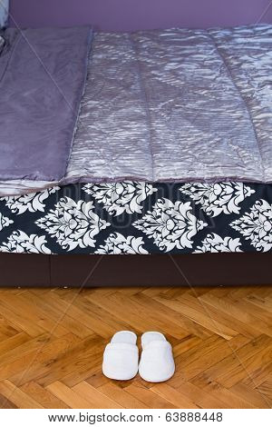Slippers on wooden floor parquet in front on bed in house