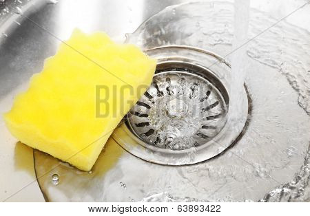 Water flowing down hole in kitchen sink