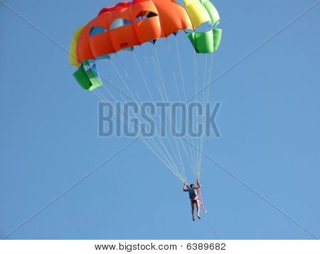 Man with colourful parachute against blue sky