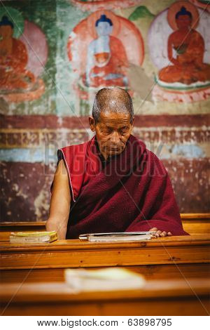 THIKSEY, INDIA - SEPTEMBER 4, 2011: Old Tibetan Buddhist monk during prayer in Thiksey gompa (Buddhist monastery)  of the Yellow Hat (Gelugpa) sect - the largest gompa in central Ladakh