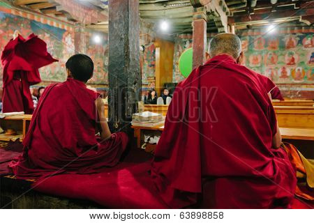 THIKSEY, INDIA - SEPTEMBER 4, 2011: Tibetan Buddhist monks during prayer in Thiksey gompa (Buddhist monastery) of the Gelugpa sect - largest gompa in central Ladakh and popular tourist attraction