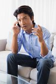stock photo of annoying  - Annoyed man sitting on couch talking on phone at home in the living room - JPG