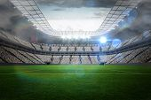 stock photo of cloudy  - Large football stadium with lights under cloudy sky - JPG