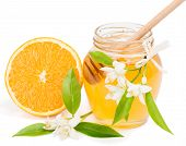 stock photo of orange blossom  - Half orange fruit blossom and opened honey jar with drizzler inside isolated on white - JPG