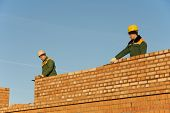 stock photo of putty  - two construction mason worker bricklayer installing red brick with trowel putty knife outdoors - JPG