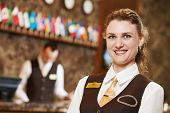 image of receptionist  - Happy receptionist female worker portrait standing at hotel counter in lobby - JPG
