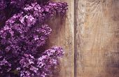 stock photo of floral bouquet  - Bouquet of lilac flowers on a wooden board floral background rustic style decoration - JPG