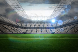 foto of football pitch  - Large football stadium with lights under cloudy sky - JPG