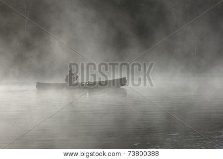 Paddling A Canoe On A Misty Lake