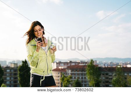 Female Athlete  Drinking Water And Messaging On Smartphone