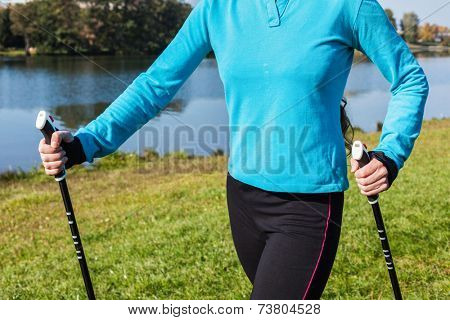 Nordic walking exercise adventure hiking concept - closeup of woman's torso and hands holding nordic walking poles