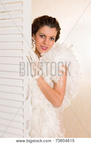 Young brunette in vintage 1920s feather boa looking from behind a folding screen in her boudoir