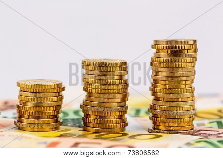 stacks of money coins rising curve, symbol photo for increasing profits and rising costs