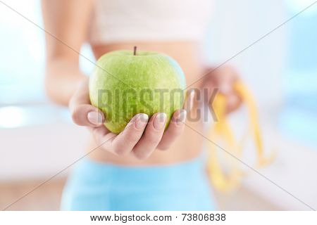 Close-up of fresh green apple held by a woman