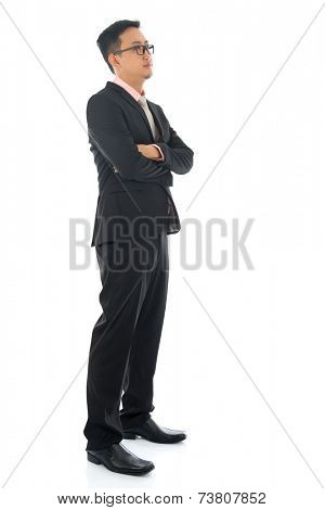 Full length confident southeast Asian business man crossed arms looking away standing isolated on white background.