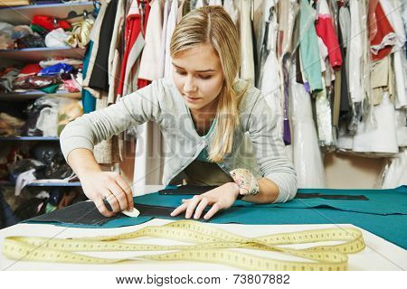 young female tailor working with cloth fabric in workshop