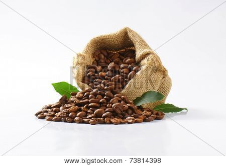 burlap sachet with roasted fair trade coffee, decorated with green leaves
