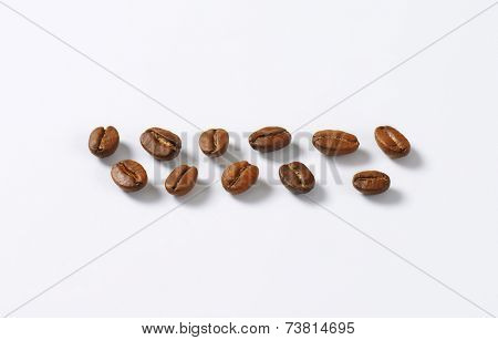 eleven selected coffee beans, formed in two lines