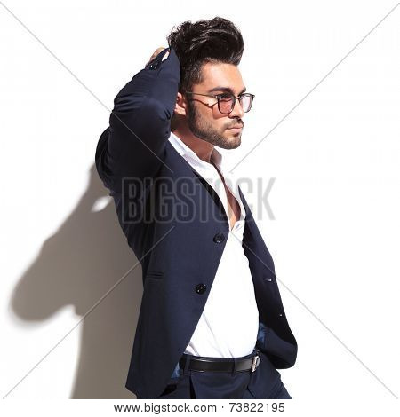 Side view of a attractive business man fixing his hair while looking away from the camera