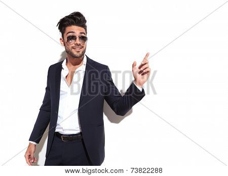 Handsome business man pointing at something to his left, looking away from the camera, against a white wall