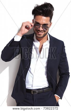 Smiling business man putting on his sunglasses while holding one hand in his pocket, looking at the camera