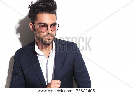 Close up picture of a handsome business man wearing sunglasses, leaning on a white wall while pulling his jacket. Looking away from the camera.