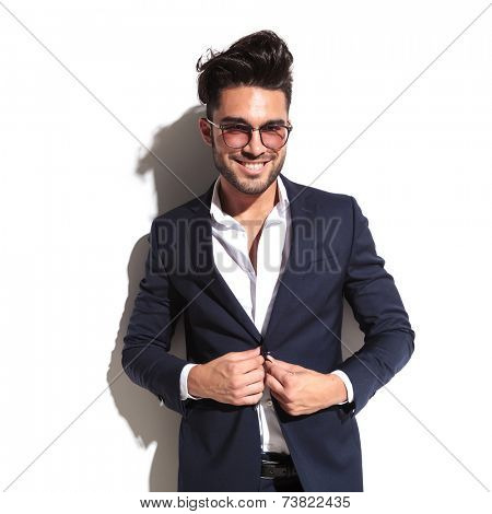 Smiling business man unbuttoning his jacket while leaning on a white wall, looking at the camera