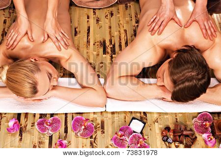 Beautiful couple getting deep back massage and relaxation at the spa salon.