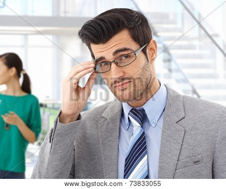 Smart handsome young caucasian bristly business expert with glasses at office. Confident, looking at camera, suit and tie.