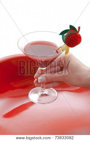 Manicured female hand holding red cocktail drink in glass. Isolated on white. Close up.