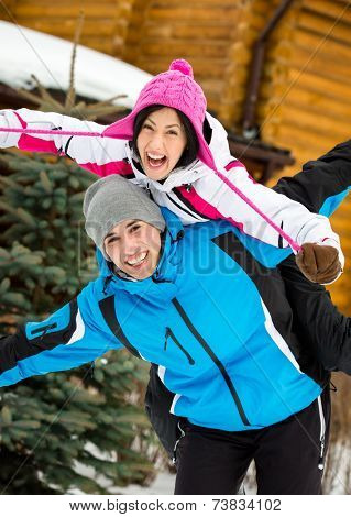 Half-length portrait of happy couple having fun outdoors during winter holidays
