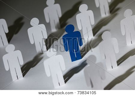 Close up of group of standing paper dolls. Lots of similar copies of a paper man, but a blue one stands out among them. Concept of teamwork and leadership