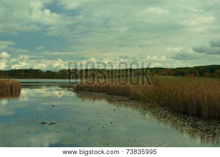 blue sky with white puffy clouds and lake
