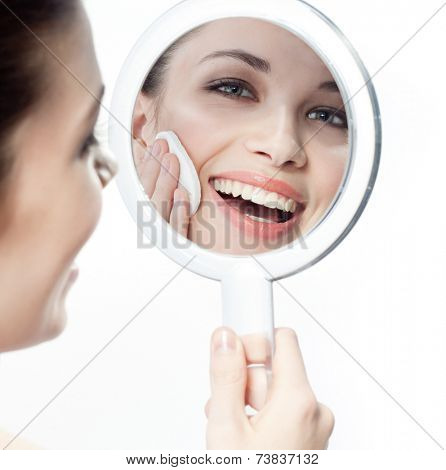 closeup portrait of attractive  caucasian smiling woman brunette isolated on white studio shot lips toothy smile face hair head and shoulders looking at mirror cleaning face cotton disc