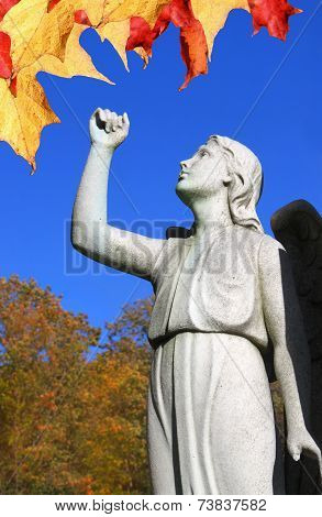 Angel Statue In Cemetary With Raised Arm And Leaves