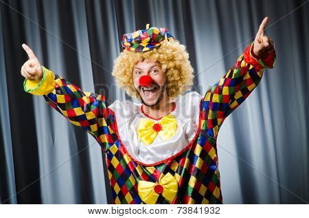 Funny clown in humorous concept against curtain