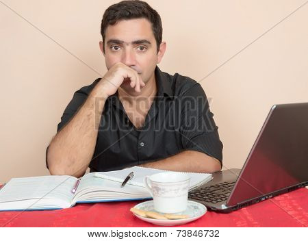 Adult education - Hispanic man studying or doing office work at home