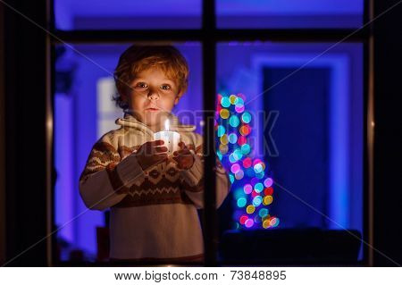 Little Toddler Boy Standing By Window At Christmas Time And Holding Candle