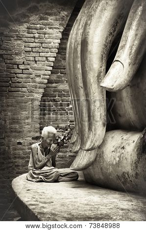 An Unidentified Old  Woman  Pay Respect To The Ancient Buddha Statue