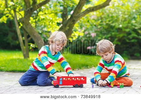 Two Twin Boys Playing With Red School Bus